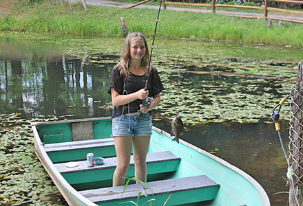 Girl on a boat with a fish on the line